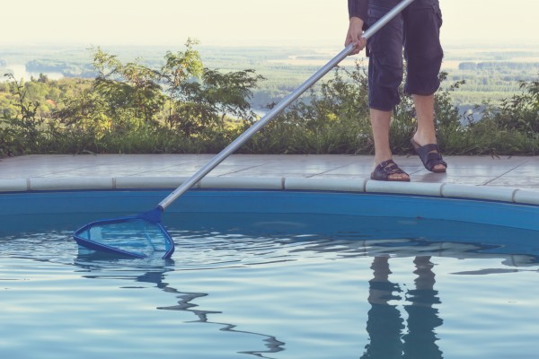 Person cleaning a swimming pool.